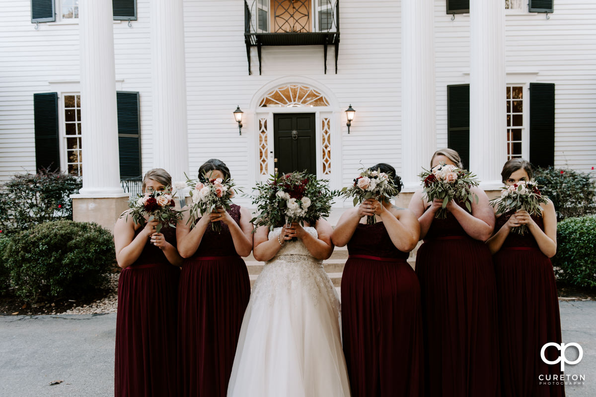 Brides holding flowers in front of their faces.