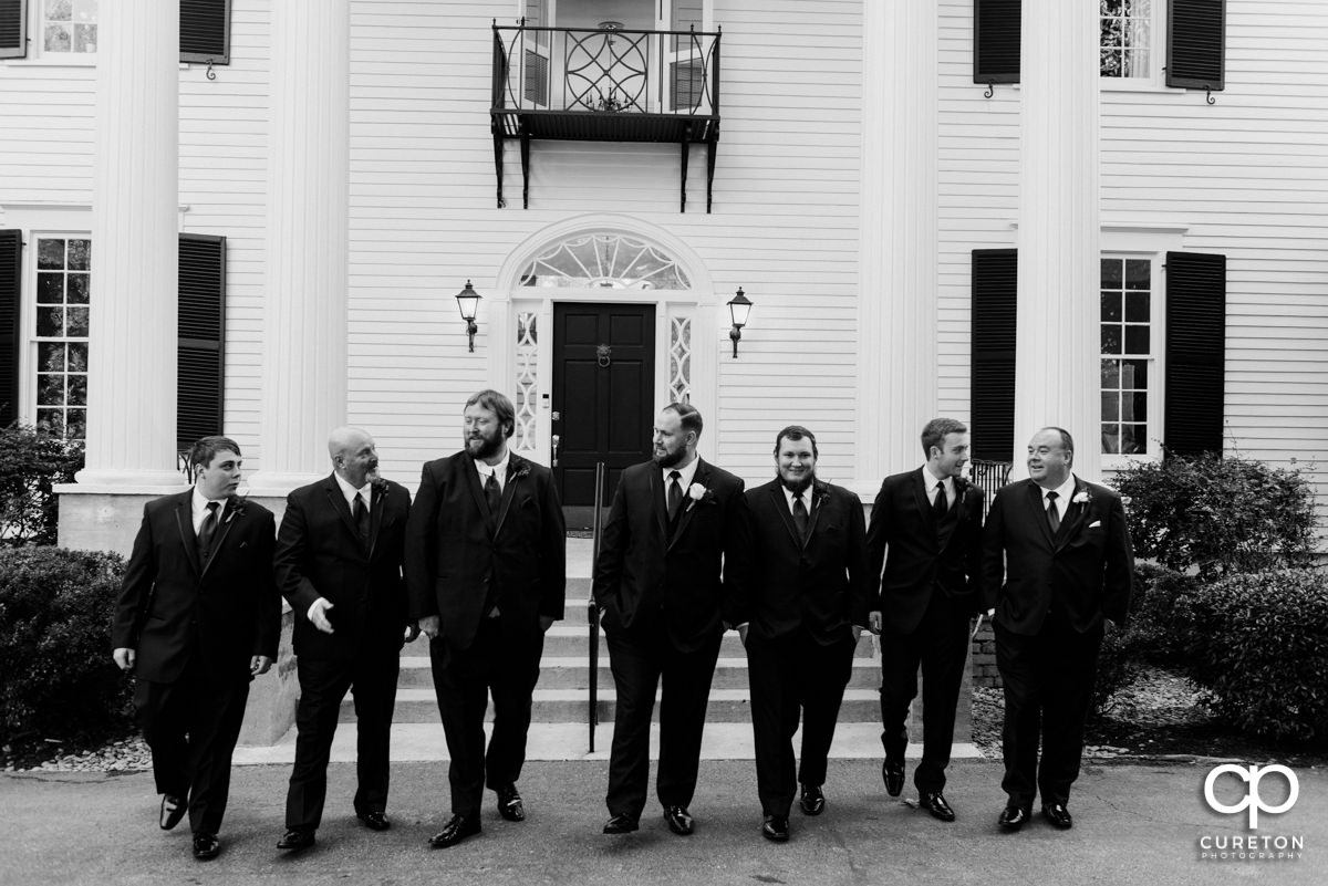 Groom and groomsmen walking in front of the house before the Duncan Estate wedding.