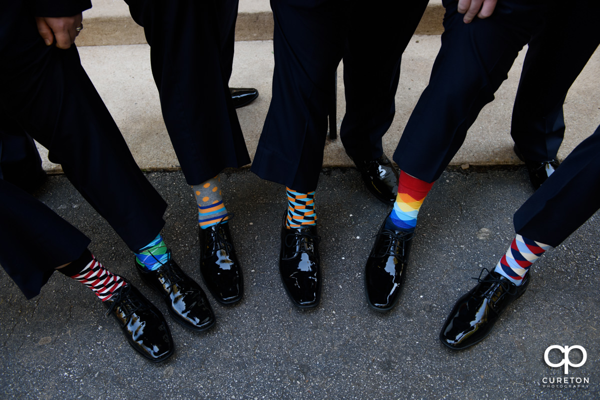Groom and groomsmen showing off their funky socks.
