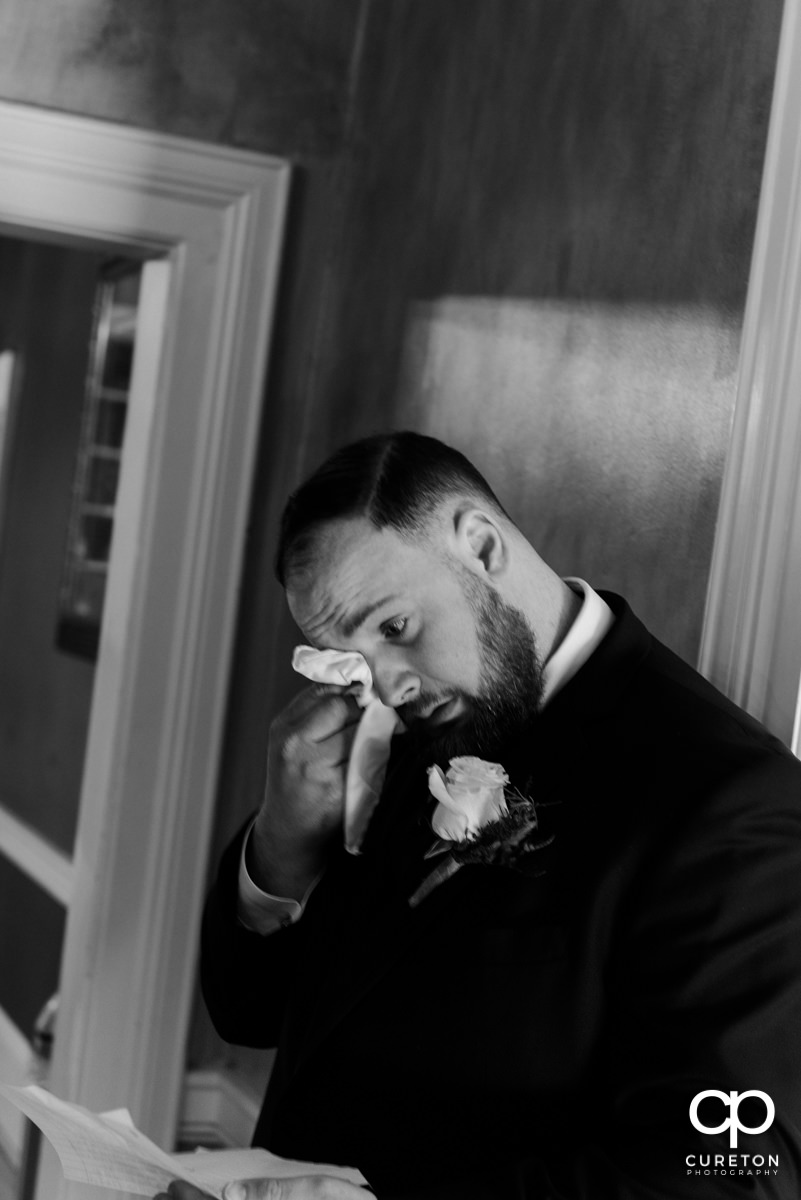Groom tearing up while praying with his bride before the wedding.