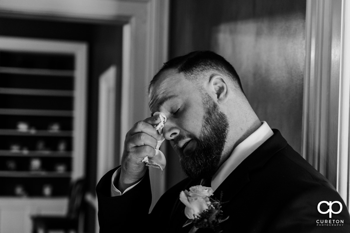 Groom wiping away tears after praying with his bride before the wedding.