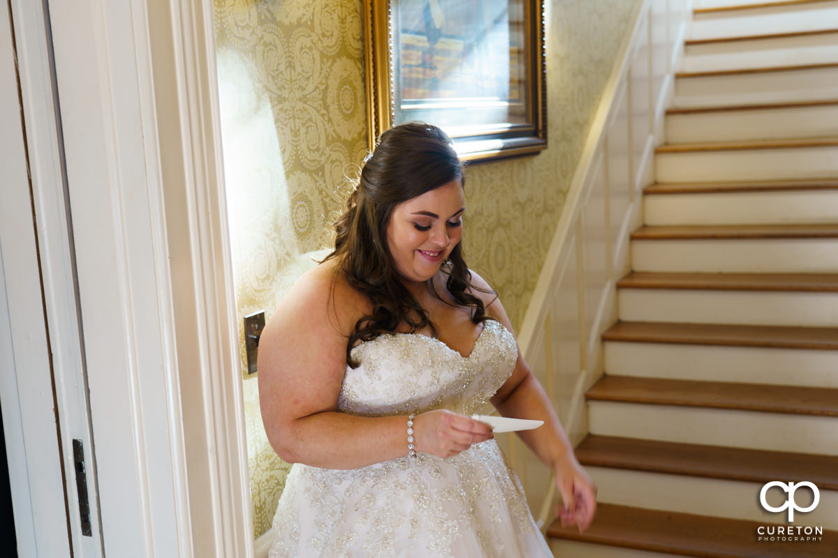 Bride smiling while reading a letter from her groom.
