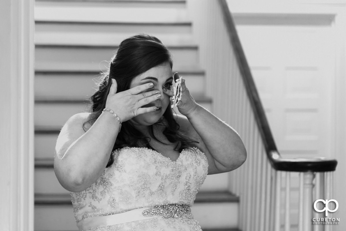 Bride wiping tears after reading a letter from her groom.