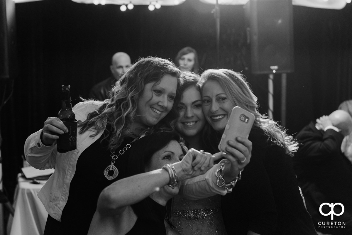 Bride taking a selfie with wedding guests.
