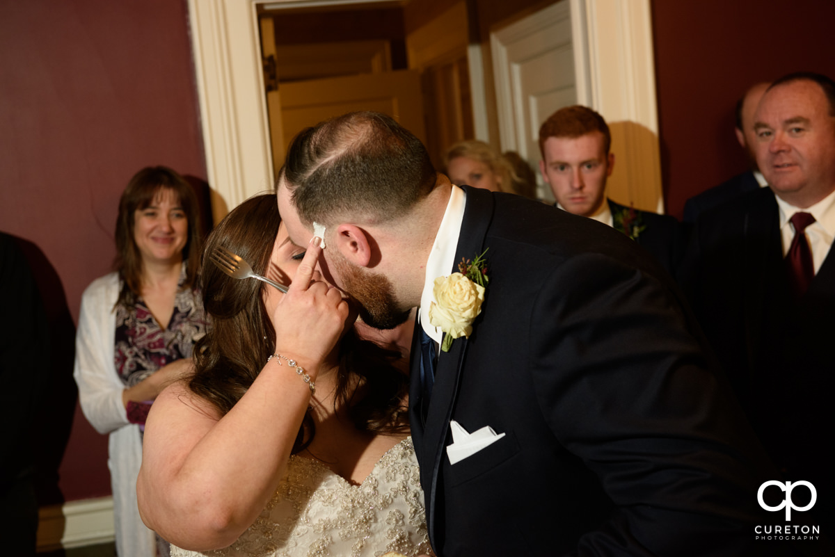 Bride wiping icing on the grooms face as they cut the cake,