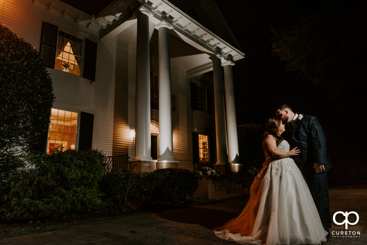 Bride and groom in front of the Duncan Estate house at night