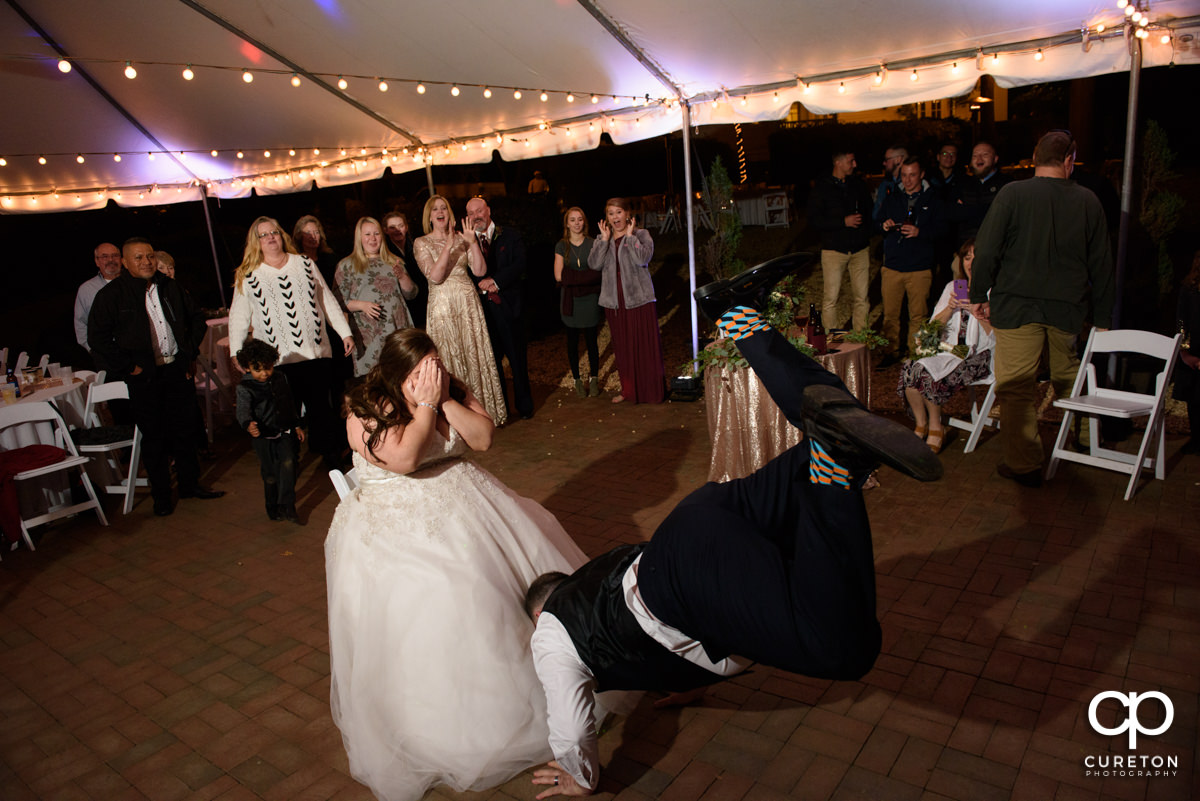 Groom jumping in the air to take off the garter.