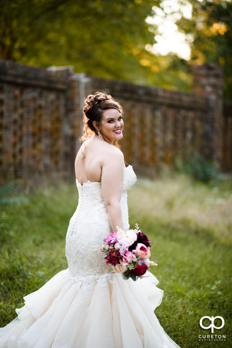 Bride smiling in a field near a wall at Edinburgh West.