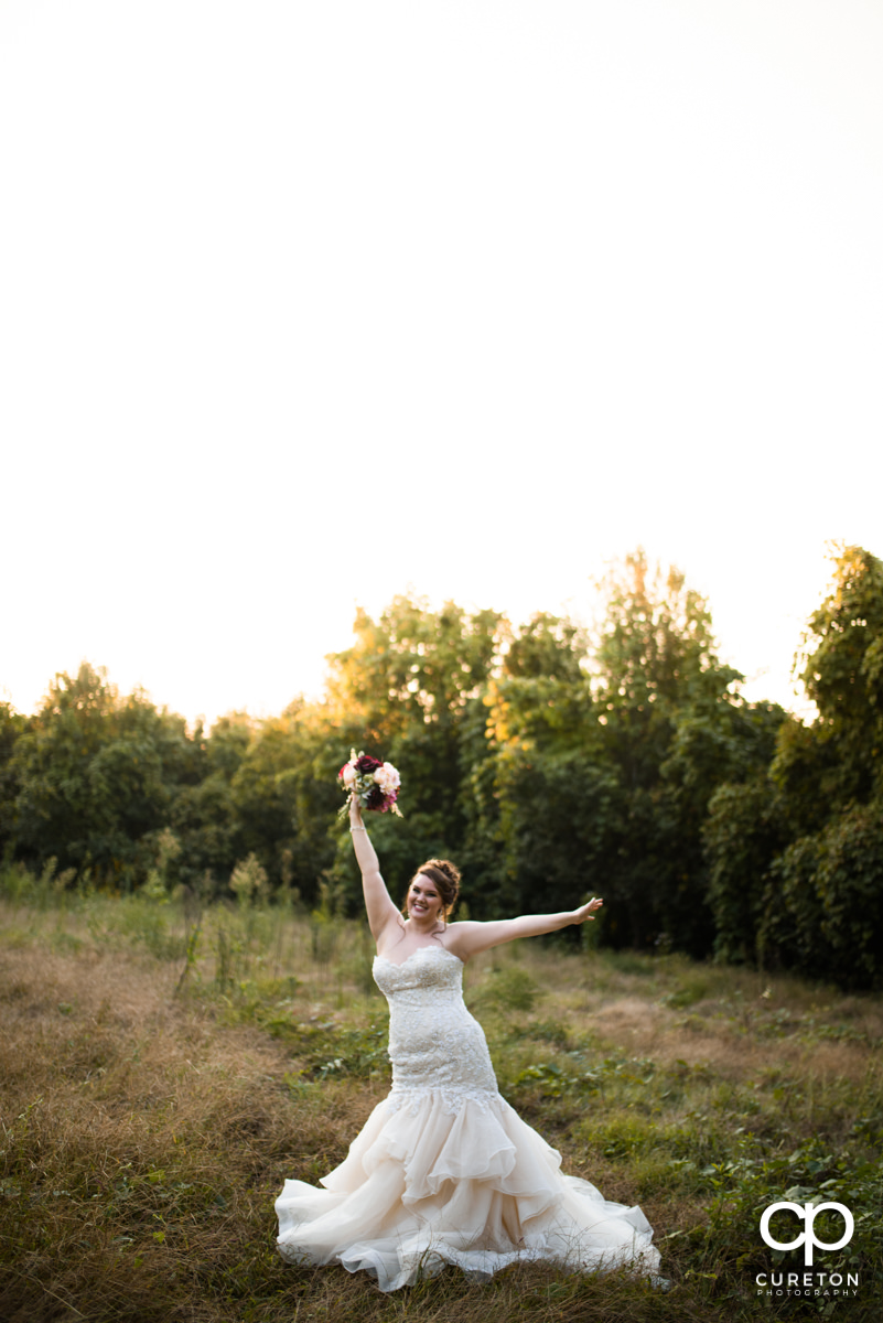 Bride with her hands in the air cheering.