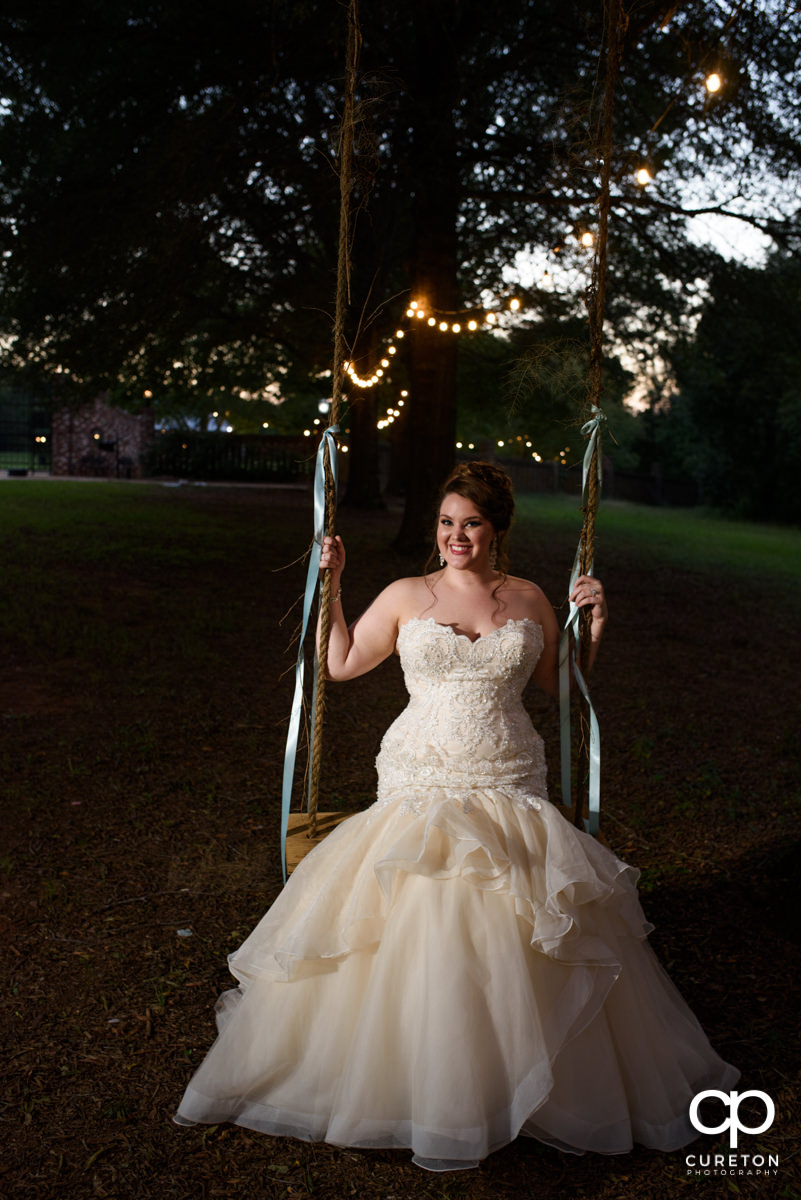 Bride sitting on a tree swing.