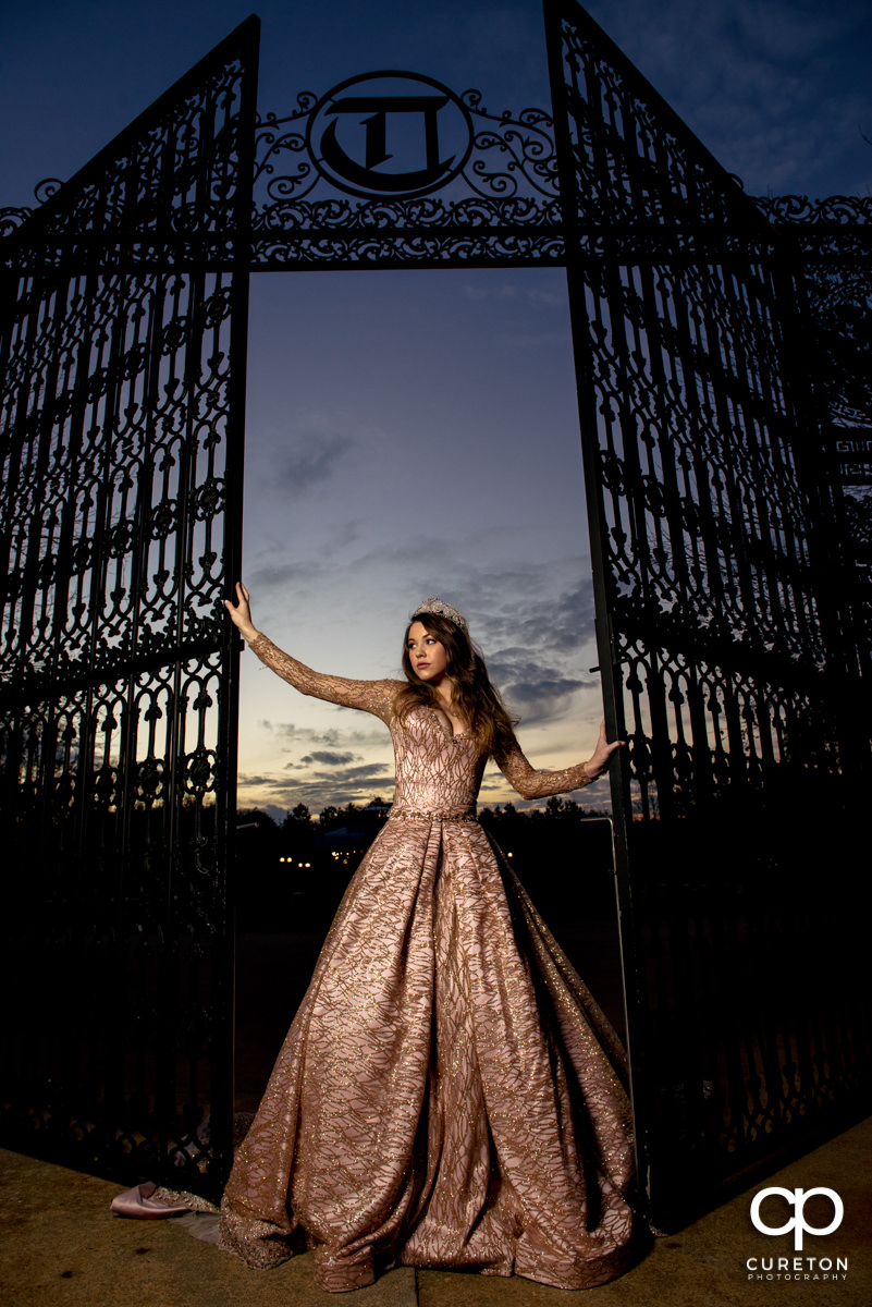 Bride at sunset holding onto an iron gate after her wedding at Edinburgh West in Greenville,SC.