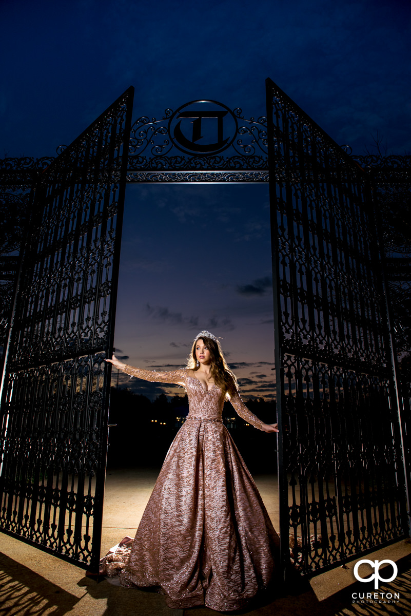 Bride backlit at sunset in front of the gates at the Edinburgh West wedding venue in Greenville,SC.