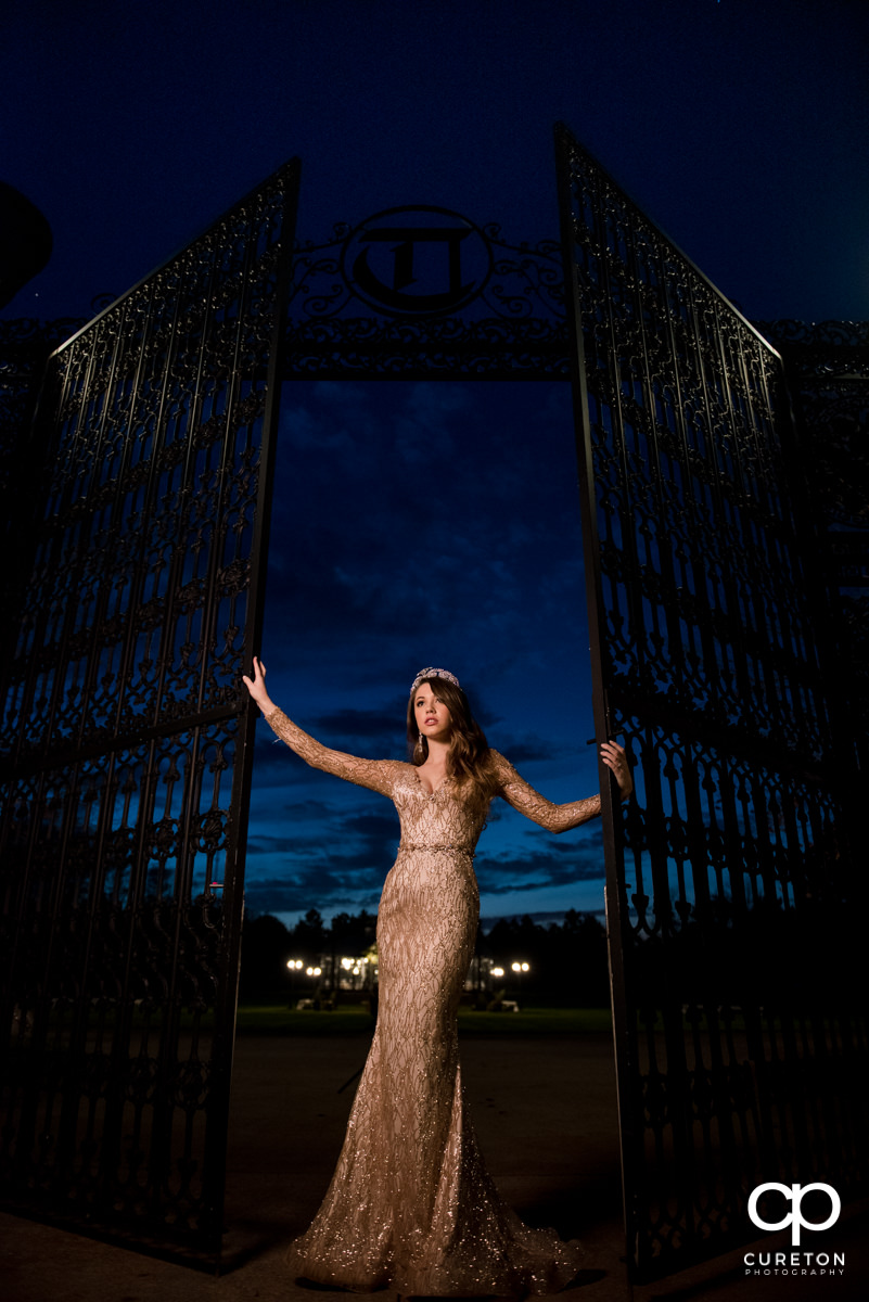 Bride at the gates at the Edinburgh West wedding venue looking into the sunset.