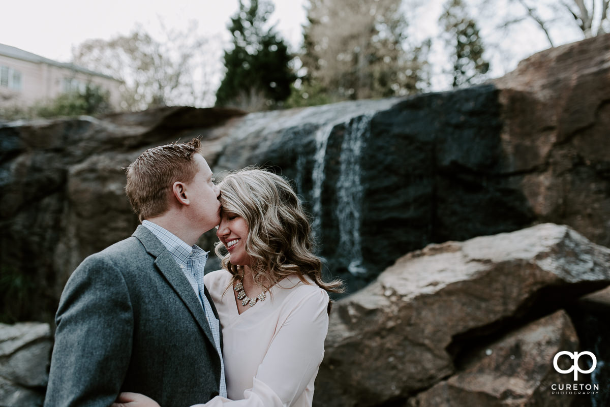 Future groom kissing his bride on the forehead in front of a waterfall during their engagement session.