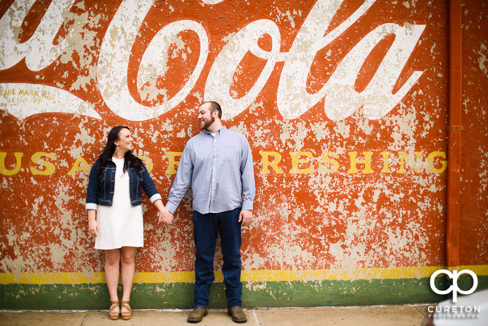 Engaged couple holding hands in front of the Coca Cola wall in downtown Greenville,SC.