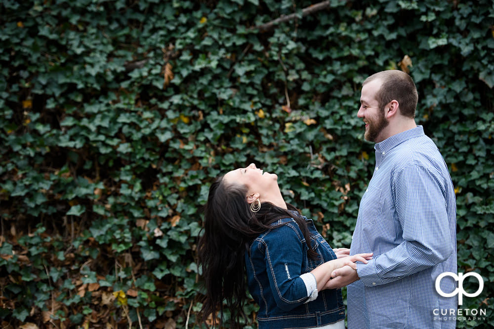 Couple laughing in front of a wall of ivy during their engagement session in Falls Park.