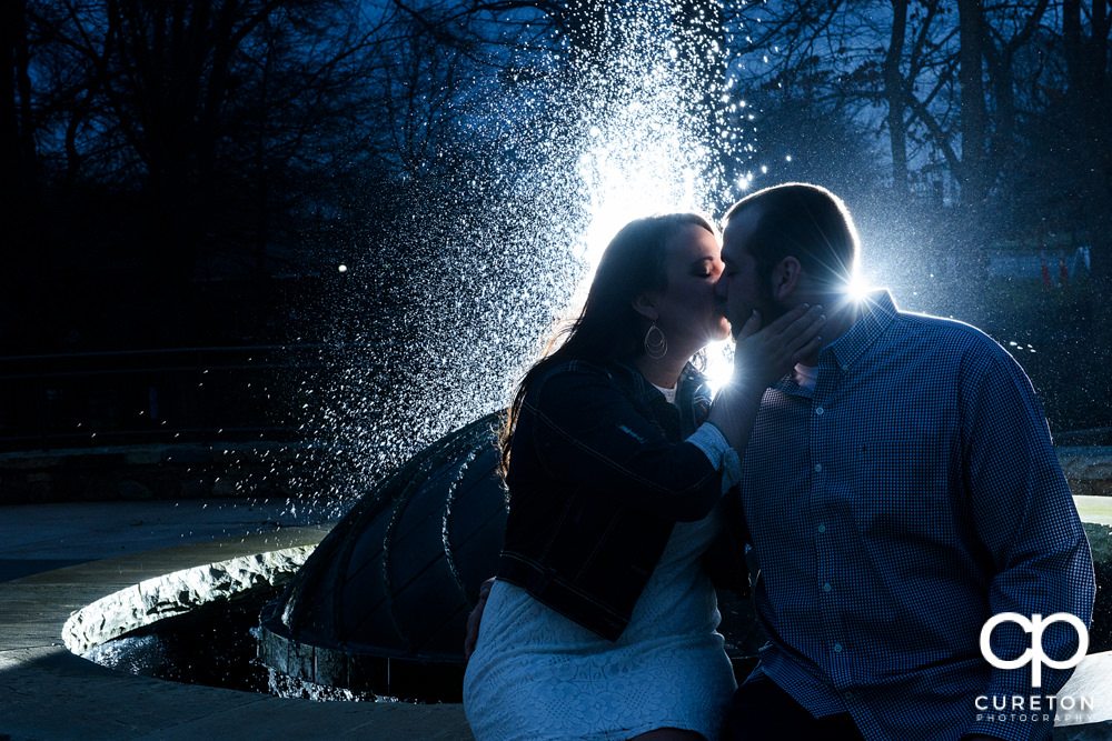 Epic backlit engagement photo of a couple hanging out at falls park in Greenville,SC .