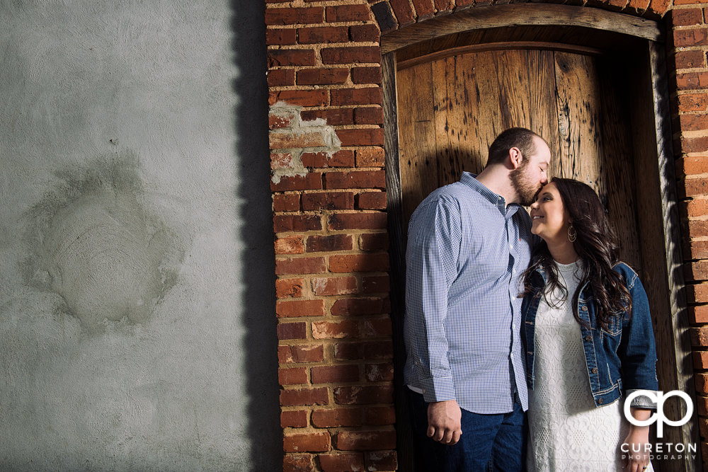 Man kissing his fiancee on the forehead inside a wooden doorway.