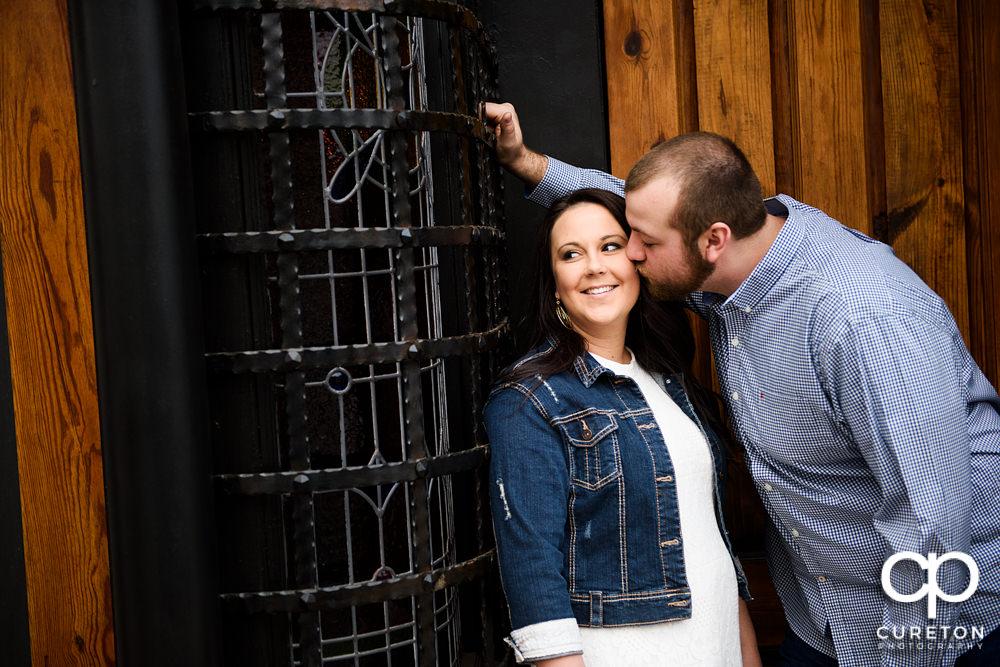 Man kissing his fiancee on the cheek.