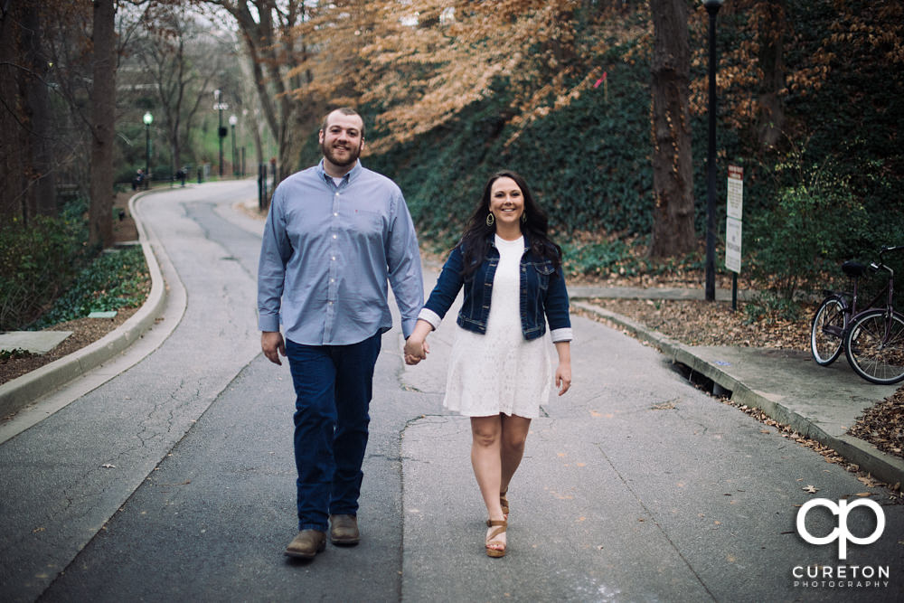 Engaged couple walking in the park.
