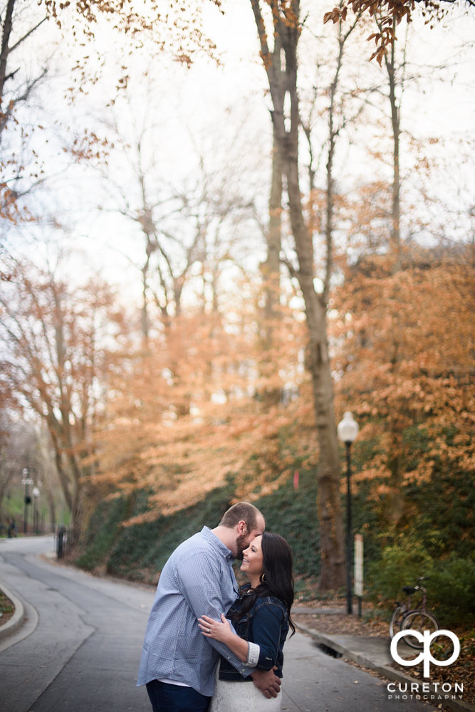 Man whispering into his fiancee's ear during their engagement session.