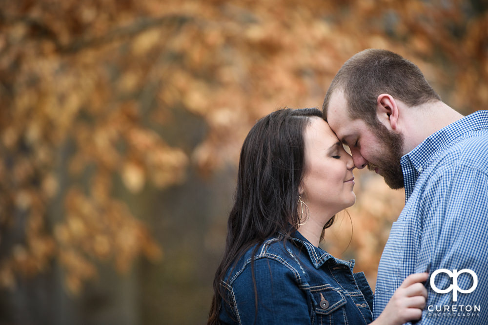 Couple nose to nose during a recent engagement session in Falls Park on the Reedy River.