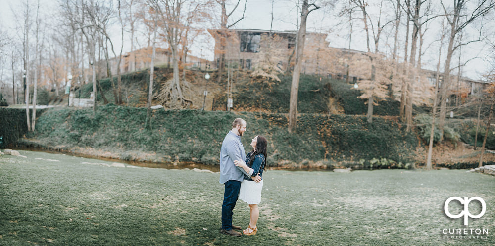 Panoramic view of Falls Park with an engaged couple near the river.