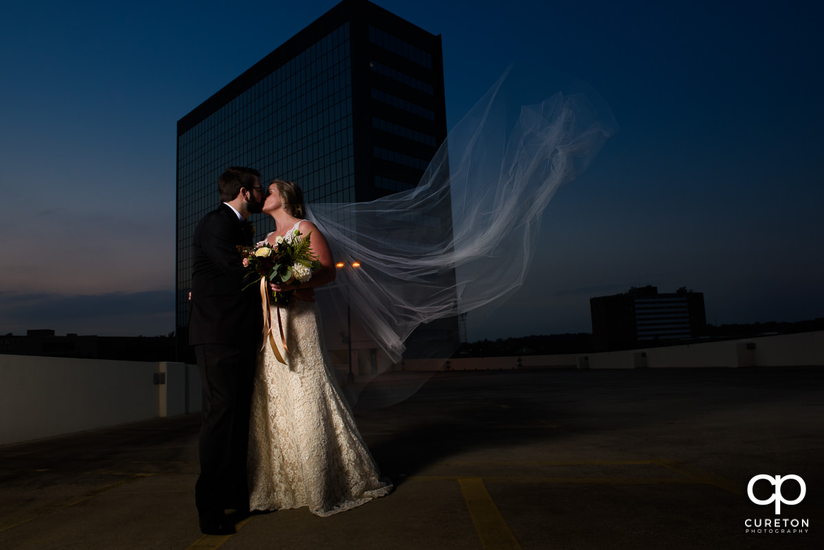 Bride and groom kissing on a rooftop with the veil blowing in the wind after their wedding at The Commerce Club in downtown Greenville, SC.