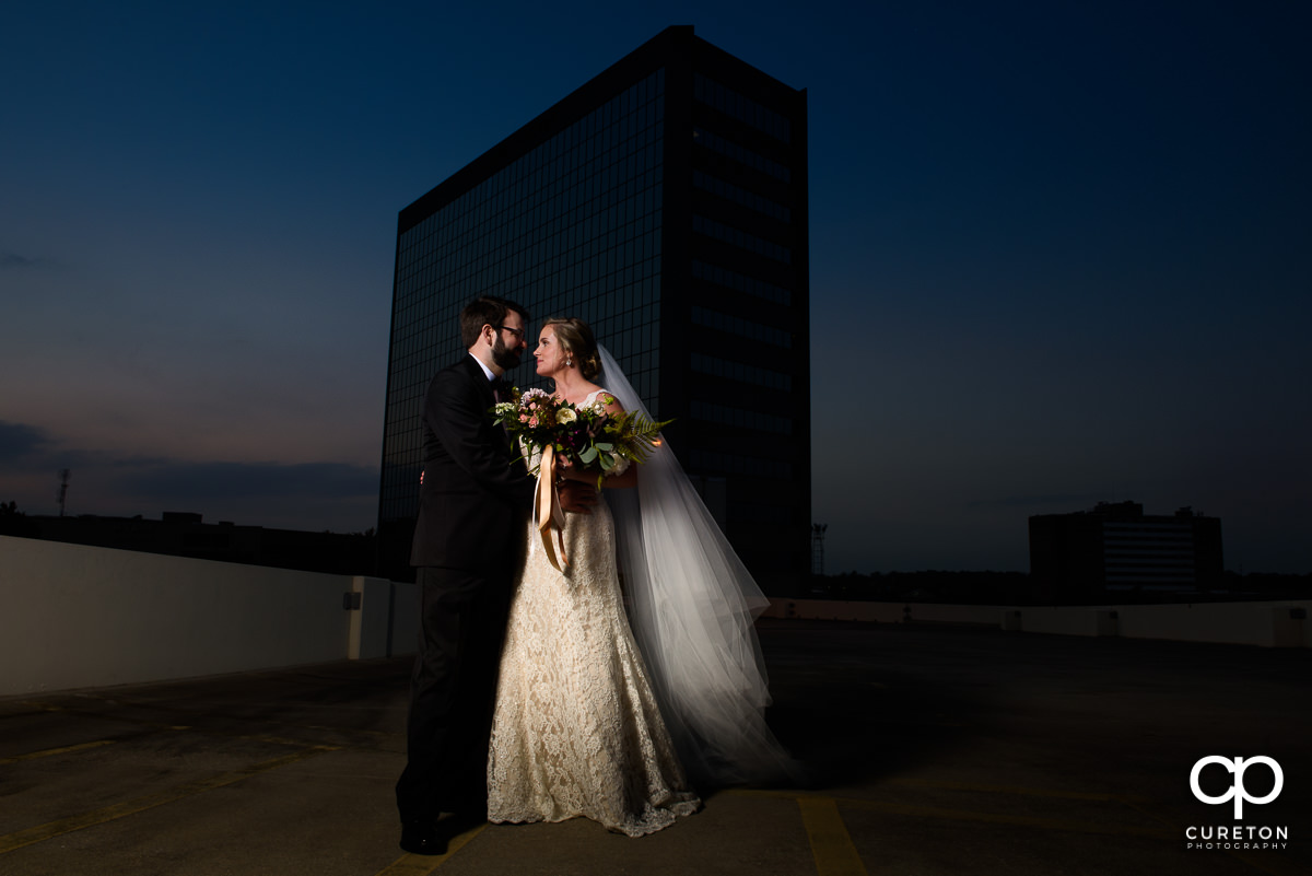 Bride and groom on a rooftop at sunset after their Commerce Club wedding.