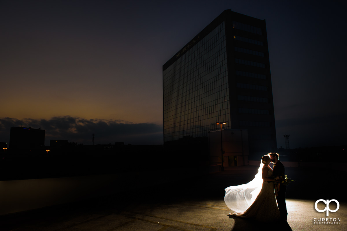 Bride and groom kissing on a rooftop at sunset with the downtown Greenville skyline in the background at their Commerce Club wedding.
