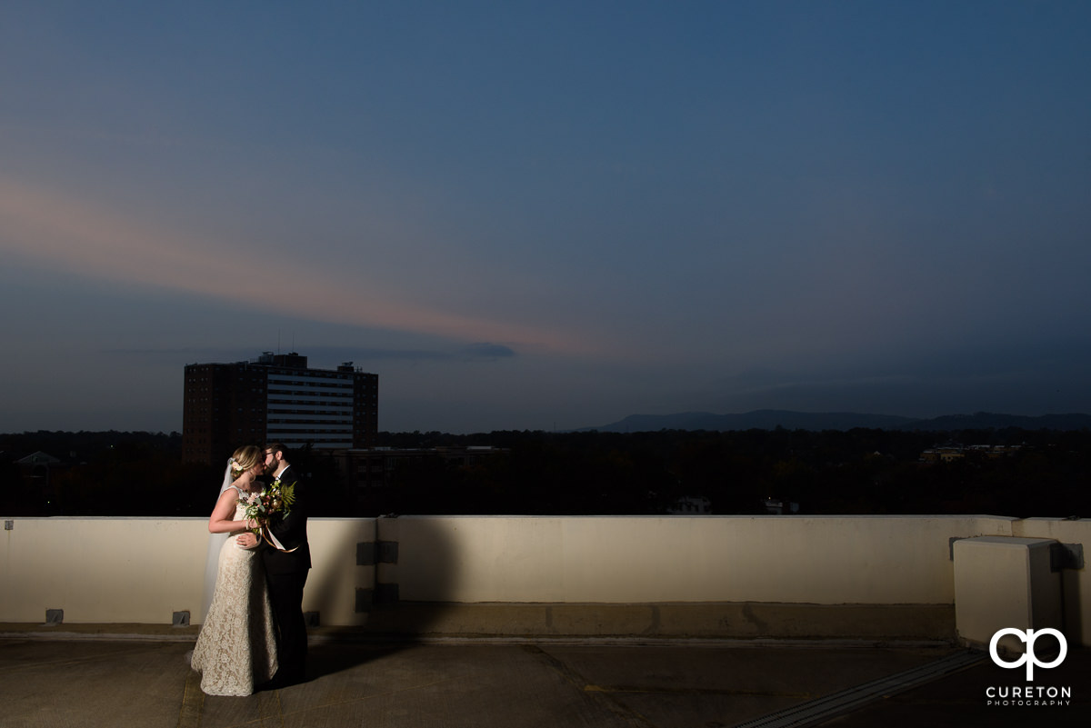 Bride and groom on a rooftop in downtown Greenville at sunset on their wedding day.