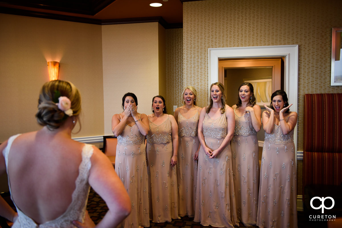 Bride reveals herself in the dress to the bridesmaids.