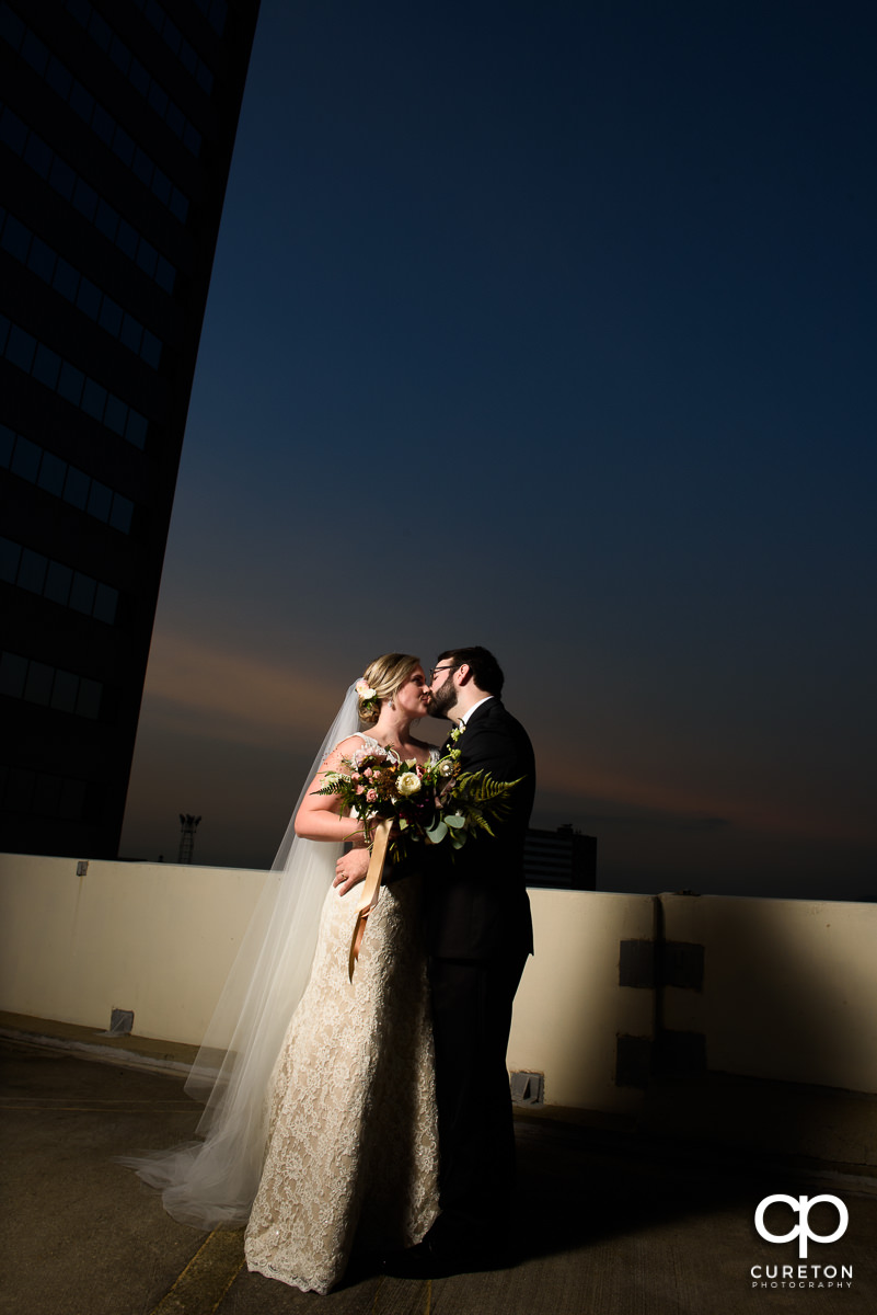 Married couple kissing on the roof in downtown Greenville at the Commerce Club during their wedding reception.
