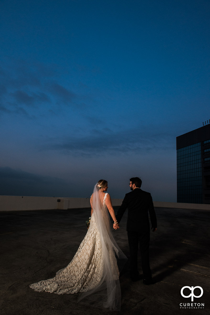 Bride and groom walking on a rooftop in downtown Greenville,SC.