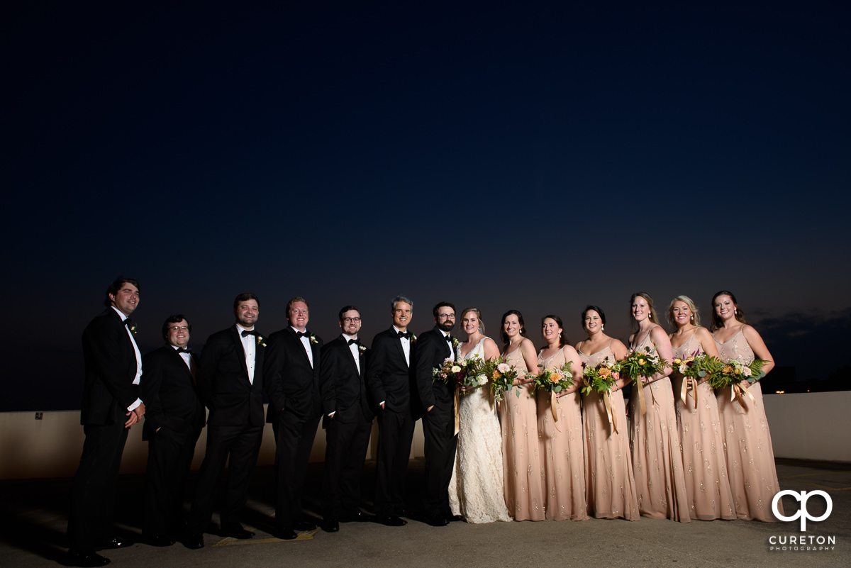 Wedding party on a rooftop in Greenville at dusk.