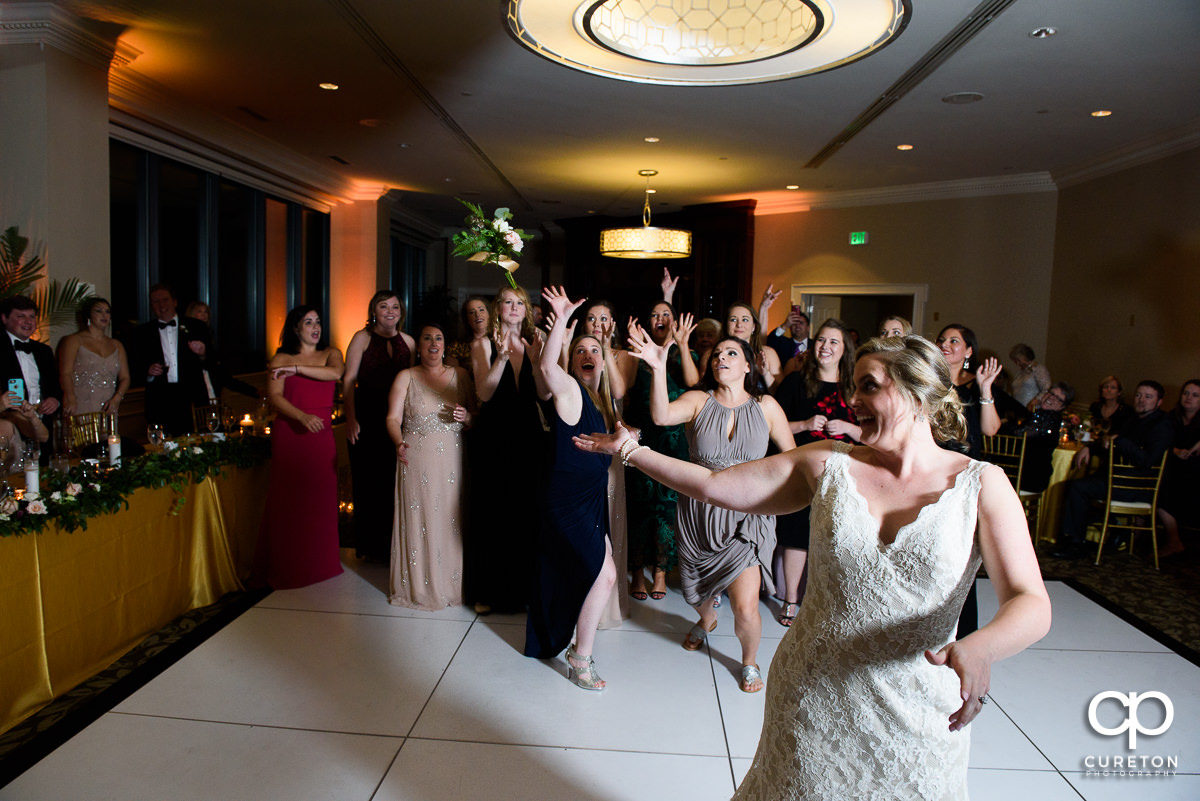 Woman scrambling to catch the bouquet at the wedding reception.