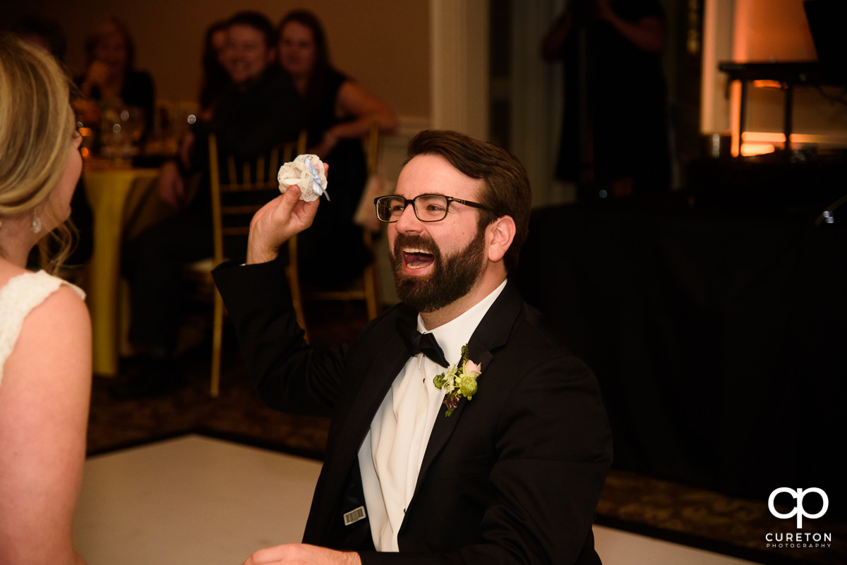 Groom holding the garter.