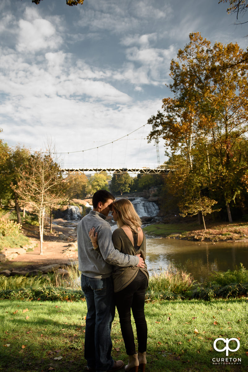 Bride and groom hugging with Liberty Bridge in the background during an engagement session in Greenville,SC.