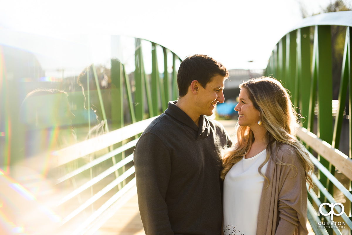 Engaged couple on a bridge over the Reedy River.