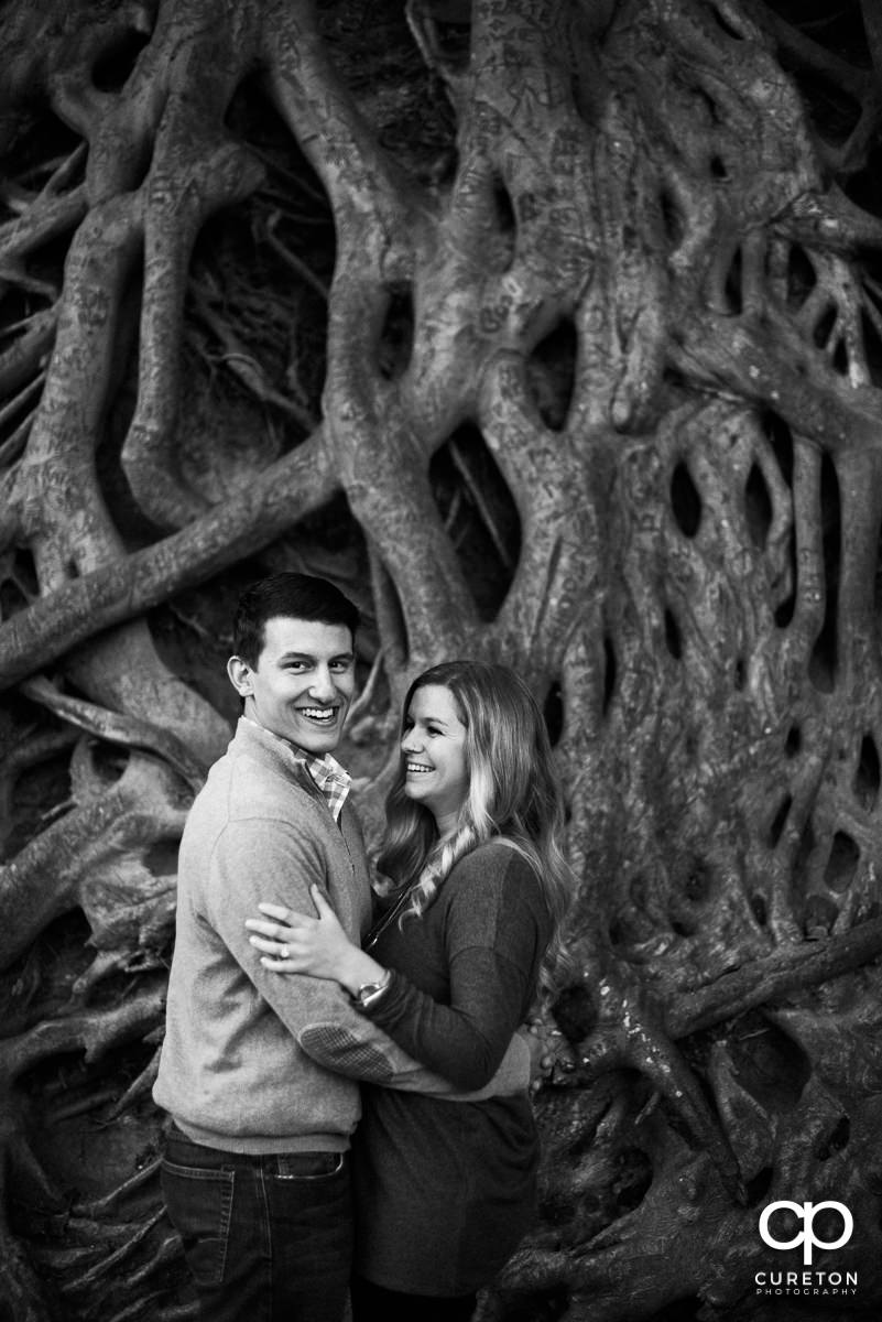 Engaged couple in front of the roots tree in downtown Greenville.