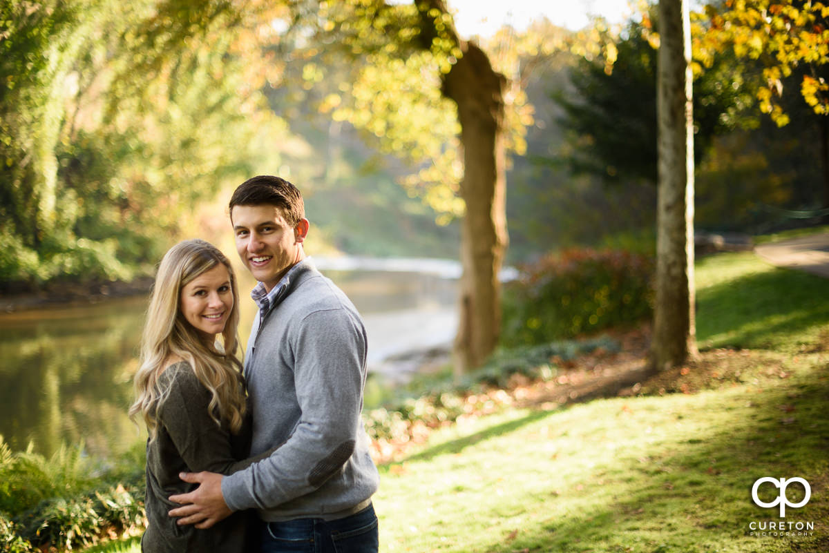 Engaged couple with fall leaves in the background.