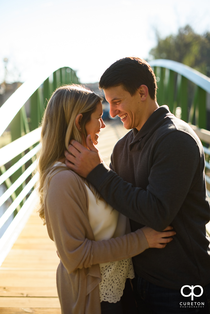 Couple laughing during their fall engagement session in downtown Greenville.