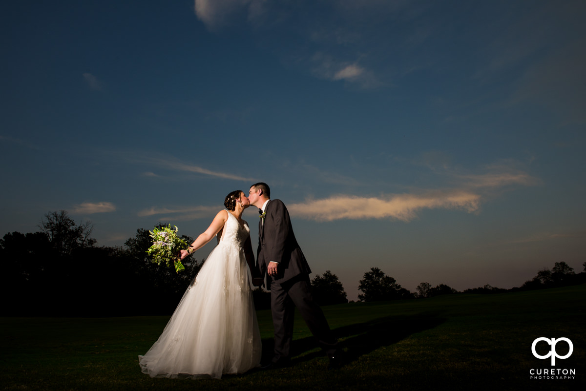Bride and groom kissing on the golf course after their Holly Tree Country Club wedding.