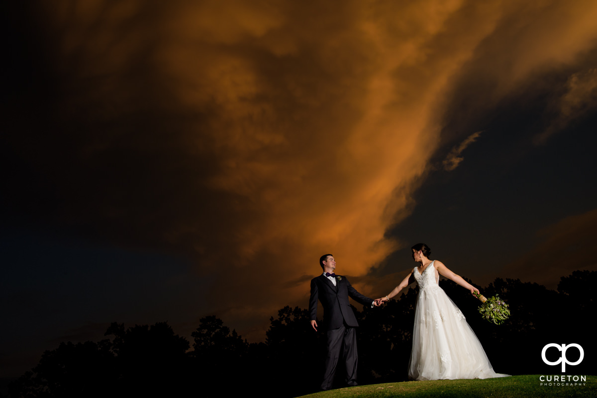 Bride and groom holding hands at sunset after their Holly Tree wedding in Simpsonville,SC.