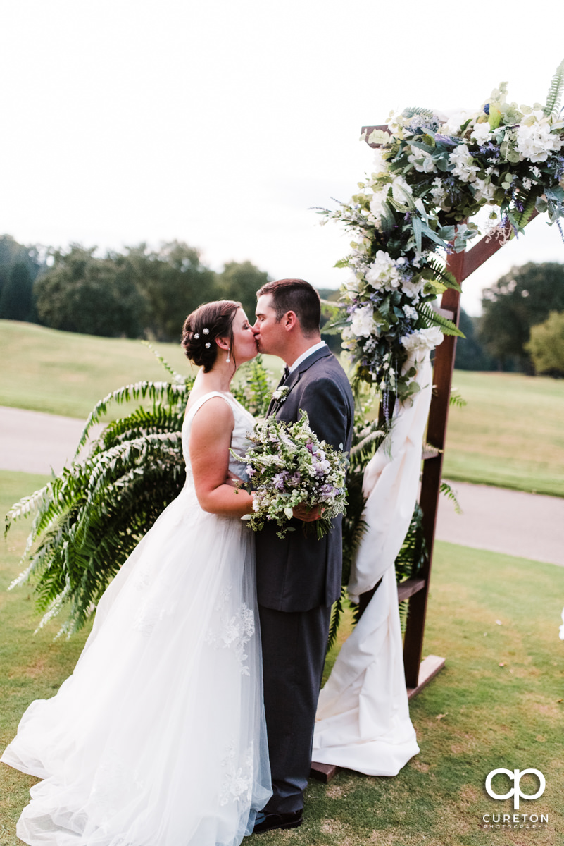Newlyweds kissing after their wedding ceremony at Holly Tree Country Club.