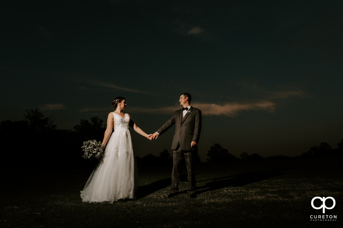 Married couple walking at sunset after their Holly Tree Country Club wedding.