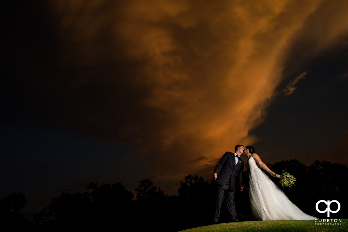 Bride kissing her groom at sunset under an amazing sky after tier wedding ceremony at Holly Tree in Simpsonville,SC.