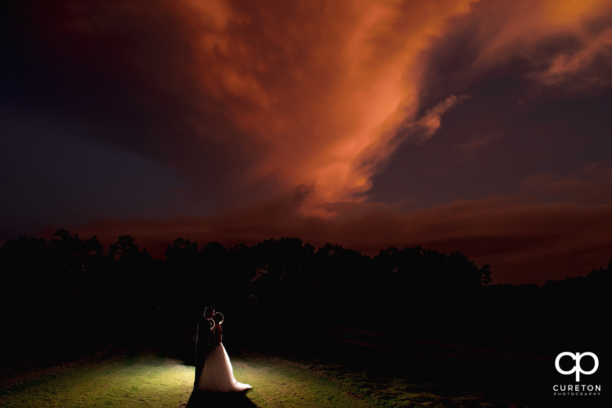 Bride and groom dancing underneath a pink sunset at Holly Tree Country Club in Simpsonville,SC.