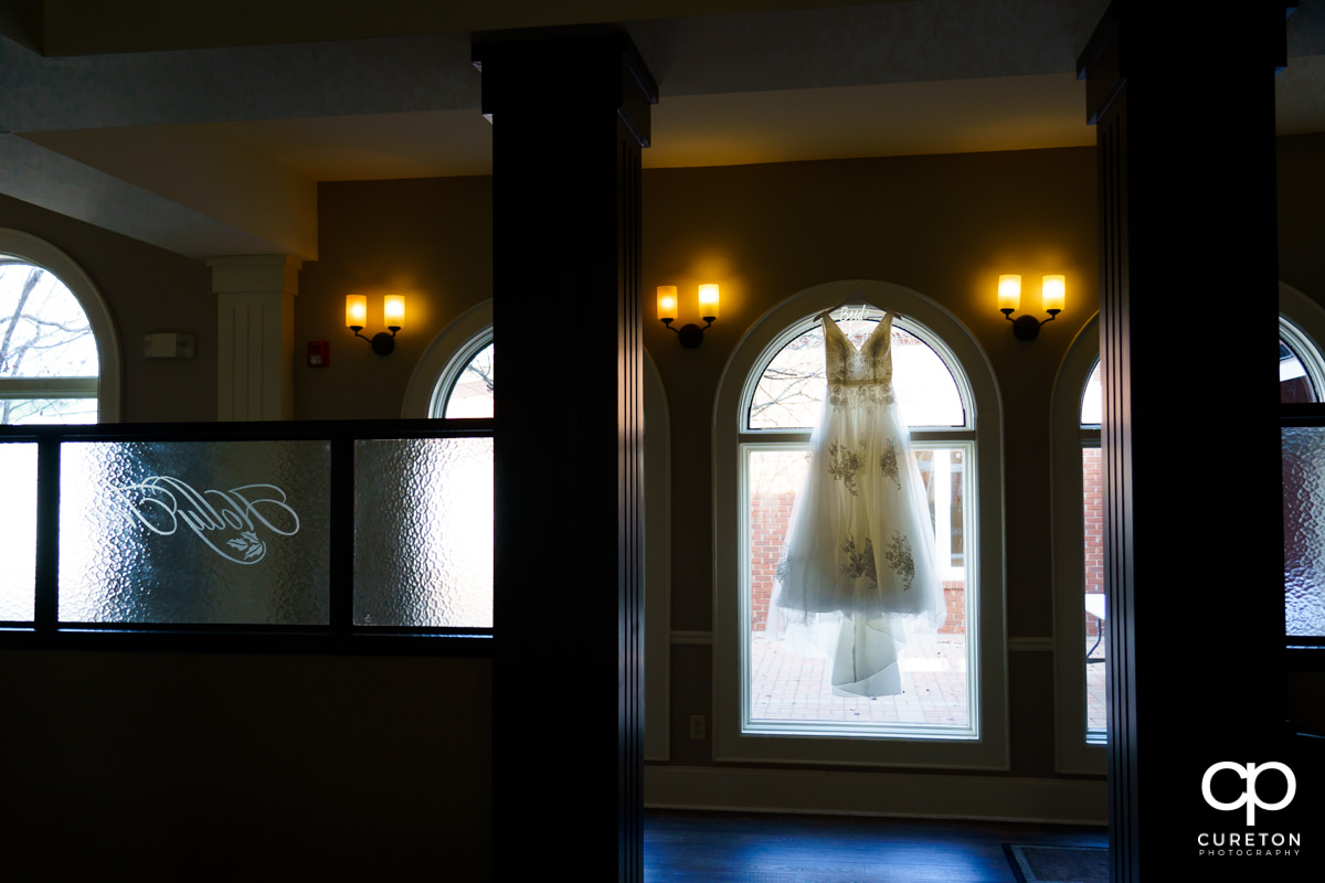 Bridal dress hanging in a window at Holly Tree Country Club.