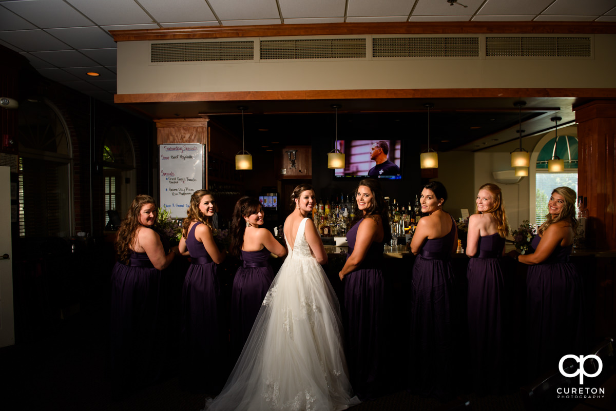 Bride and her bridesmaids sitting at the bar before the wedding.